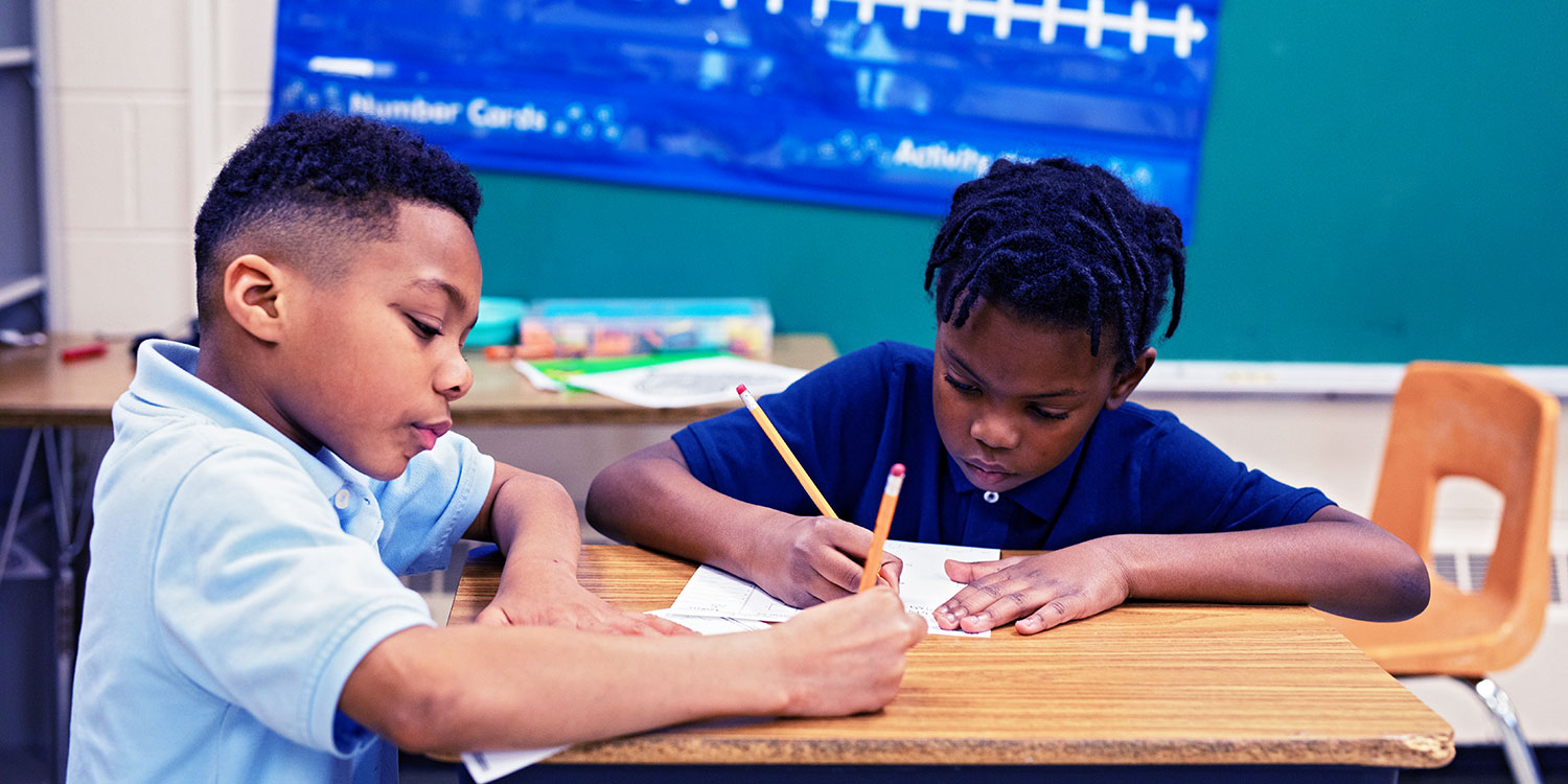 Two students completing classwork with pencils at a desk.