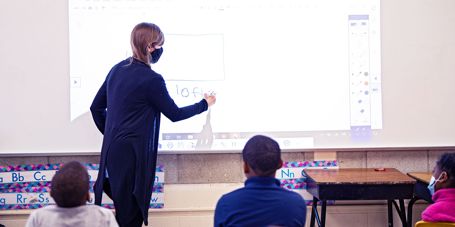 Teacher writing on white board at the front of a class.