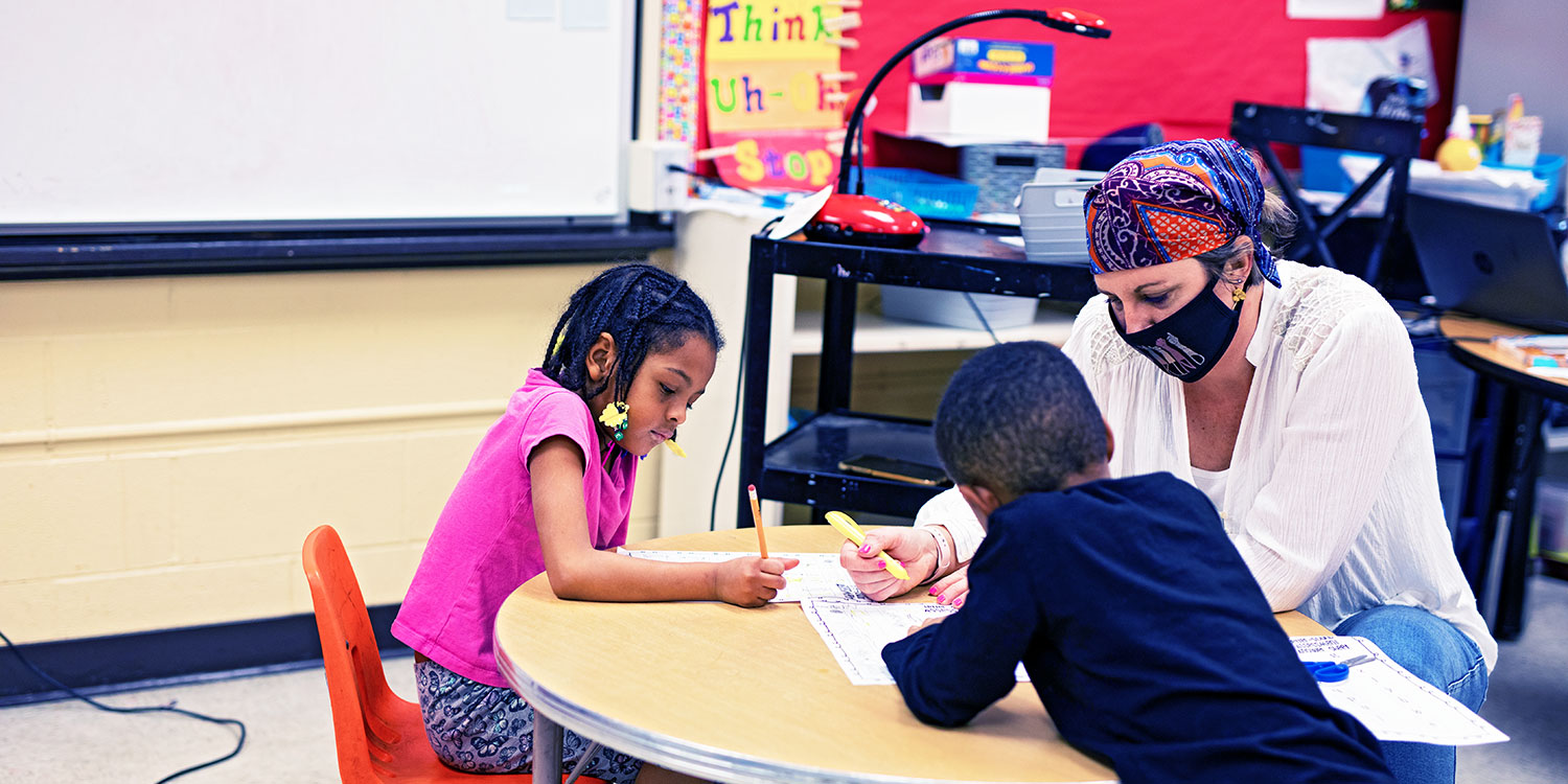 Teacher helping two students at a table.