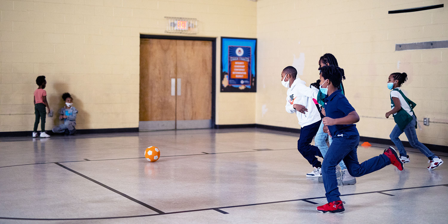 Students running after a soccer ball.